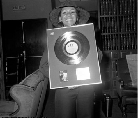 A great picture of Dame Shirley Bassey with her Gold Record for The Singles Album